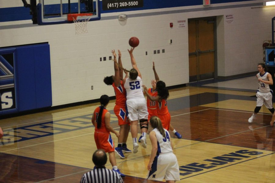 Senior Katie French jumps over opposing team members to get the ball in the basket.